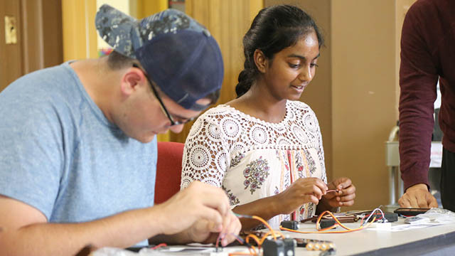 Boy and girl working on engineering project with wires