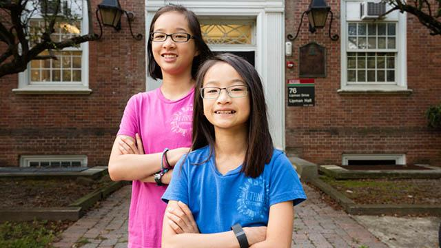 Two young girls stand outside of an academic building